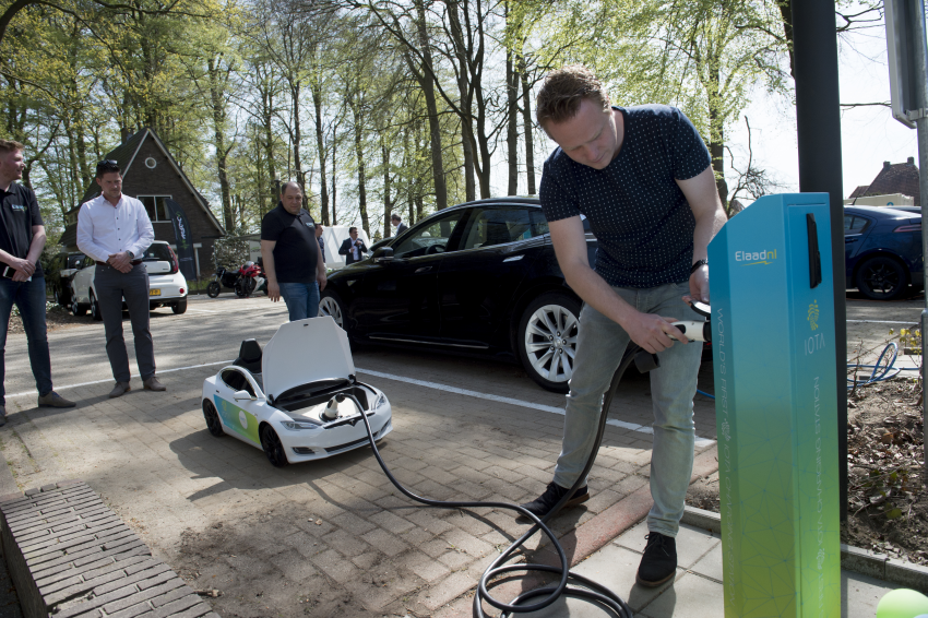 Harm van den Brink, innovator at ElaadNL and Enexis is charging a mini Telsa on the IOTA charging station at the ElaadNL test site in Arnhem, the Netherlands. (PHOTO available in high resolution at ElaadNL)